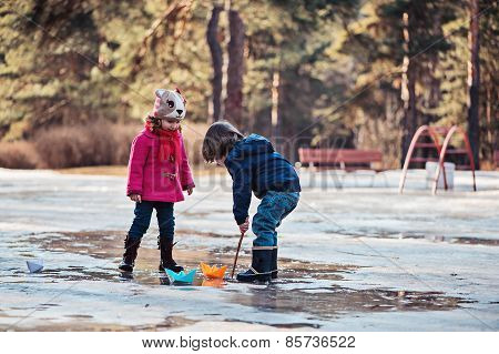 toddler boy and girl having fun playing in spring puddle with paper boats