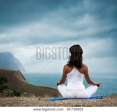 Woman Practicing Yoga at Stormy Sea