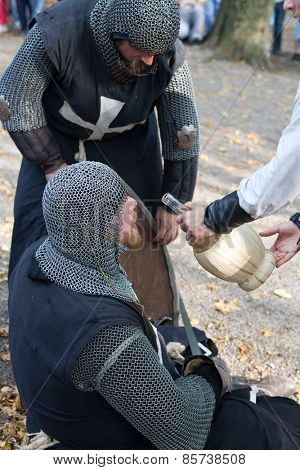 ZAGREB, CROATIA - OCTOBER 07, 2012: Squire helping injured knight with a drink after the battle at