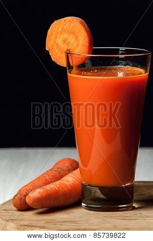Fresh carrot juice in a tall glass with purple tubes and carrots on a wooden table top