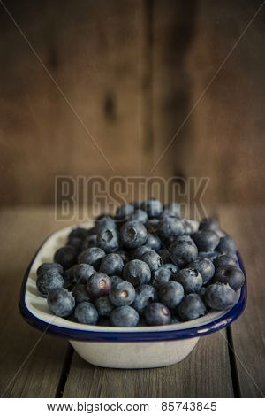 Blueberries In Rustic Kitchen Setting With Old Wooden Background With Added Texture Filter