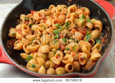 Gomiti elbow pasta shells in arrabbiata tomato, garlic and chili sauce, garnished with chopped parsley, cooking in a frying pan.