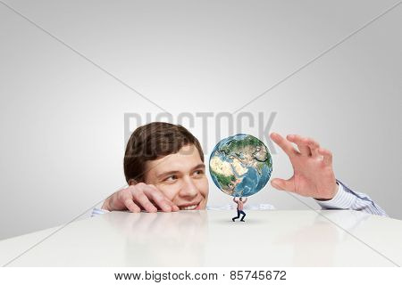 Businessman looking from under table at man lifting Earth planet. Elements of this image are furnished by NASA