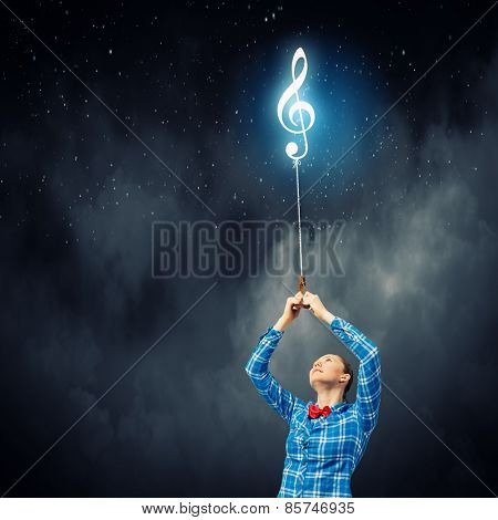 Young woman holding music sign on rope