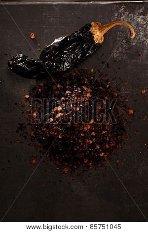chipotle - jalapeno smoked chili flakes and whole on metal background