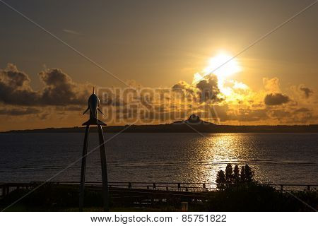 Sunset over the island and dolphin monument