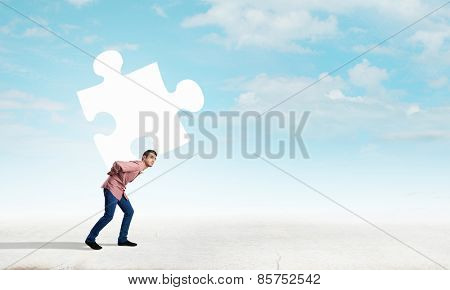 Young man in casual carrying puzzle element on back