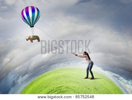 Young woman holding flying rhino on rope