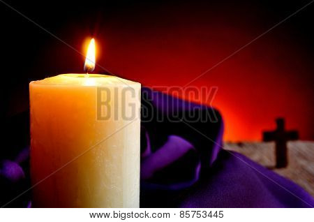 closeup of a lit candle with a purple drapery in the background and a Christian cross, on a wooden rustic surface and a red lighted background
