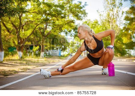 young beautiful sportswoman outdoor doing exercises