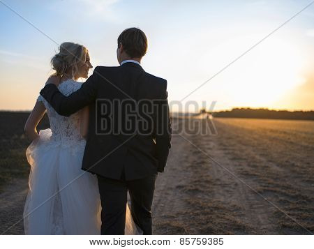Young wedding couple talking in an embrace on the field at sunse