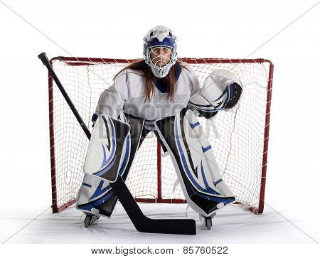 Young female ball hockey goalie guards net