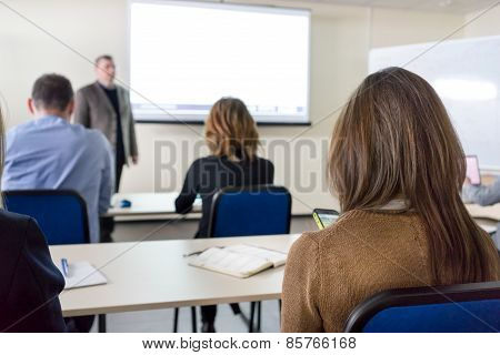 People Sitting Rear At The Desks In The Education Class And The Lecturer Near The White Desk