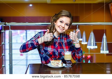 Girl In Plaid Shirt Shows Like To Cup Of Mokachino And Cake