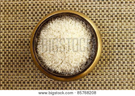 White variety raw rice kept in a bowl on a plain background