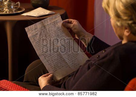 Senior Woman Reading Yellowed Letter