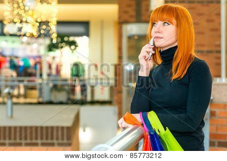 Portrait Of A Girl With A Phone And Bag Lost In Thought