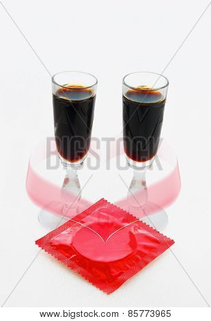 Red Condom  And Two Glasses With A Dark Drink