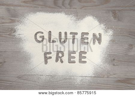 Word gluten free written in white flour on a old wooden table, vintage tone.