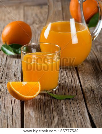Orange Juice Glass And Fresh Oranges With Leaves