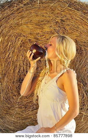 Happy woman drinking milk from cruse or crock
