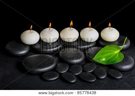 Spa Concept Of Row White Candles And Green Leaf On Black Zen Stones Background With Dew, Closeup