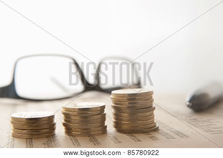 Stack Of Coins On Newspapaer