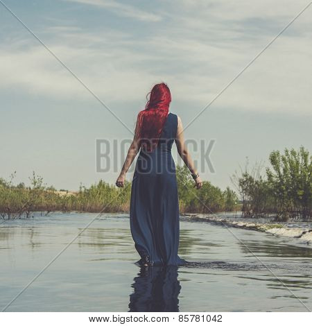 red-haired woman walking in the river