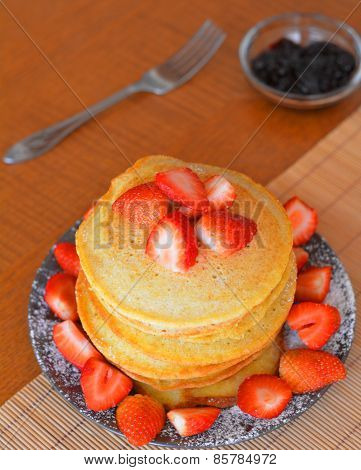 Stack of sweet pancakes with fresh strawberries and icing sugar