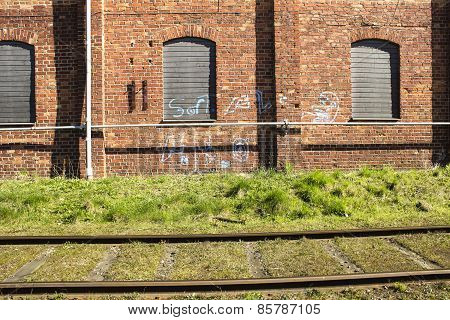 Freight Train Railroad Grass And Pipes On Old Brick Building