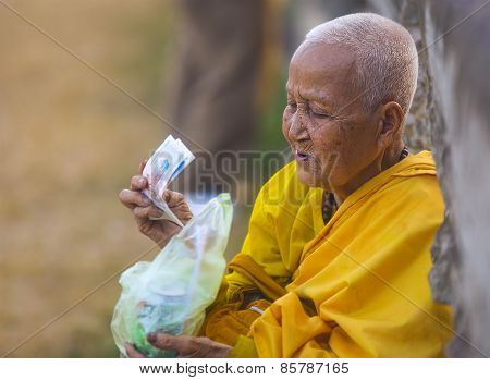 An Unidentified Old Buddhist Female Monk Dressed In Yellow Toga At Angkor Wat Temple.