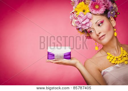 Young healthy woman holding gift box on her palm