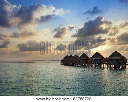 Houses over the sea at sunrise. Maldives