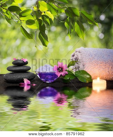 Candle, towels, black stones and purple flower on water