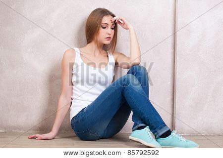 The Thoughtful Girl Sits On A Floor Near A White Wall