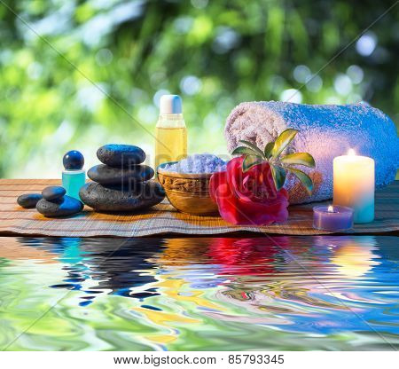 stones, candle camellia oil salt towel on water