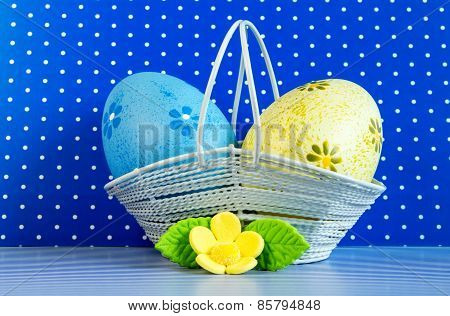 Blue And Yellow Easter Eggs In A Basket With Yellow Flower