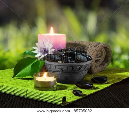 jar of black stones and candles on green mat