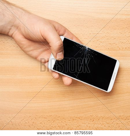 Hands holding a phone with a broken screen