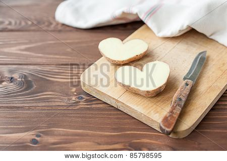 Heart shaped potato on the plank with knife