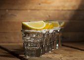 image of shot glasses  - Tequila in shot glasses with lemon and salt on wooden background - JPG