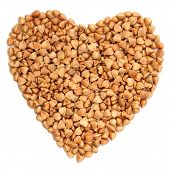 stock photo of buckwheat  - Wholegrain buckwheat in heart shape isolated closeup macro - JPG