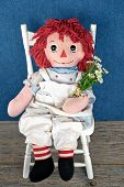 stock photo of rag-doll  - Old rag doll with daisy bouquet sitting on a white chair - JPG