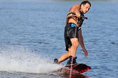 foto of watersports  - Wakeboarder in blackl shorts riding in sunset - JPG