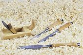 image of chisel  - Three chisels and one spokeshave lying in wooden shavings - JPG