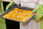 stock photo of pot roast  - Woman holds homemade roasted meat with cheese and pineapples at baking tray - JPG
