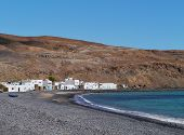 stock photo of negro  - The bay and the white houses of the fishing village Pozo Negro at the Atlantic ocean on the Island Fuerteventura belonging to Spain - JPG