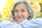 image of single woman  - Portrait of a happy happy senior woman in autumn park - JPG