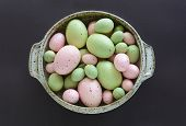 pic of aubergines  - Hand crafted colorful easter eggs inside speckled pottery bowl on aubergine background - JPG