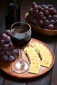 foto of wine grapes  - Glass of red wine with red globe grape crackers and a bottle of wine photographed on dark wood with natural light  - JPG